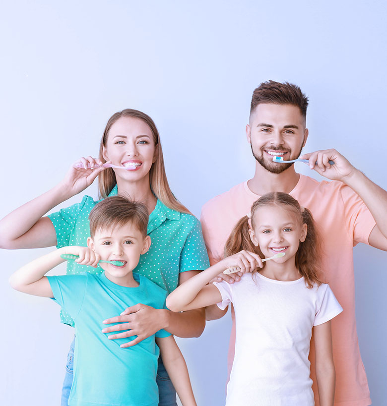 Portrait of family brushing teeth on light background
